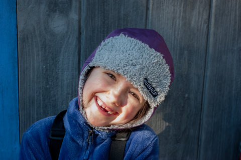 Child smiling in winter trapper hat by Villervalla Sweden at US Biddleandbop.com