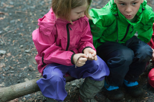 boy and girl sitting on log in raingear for Biddle and Bop