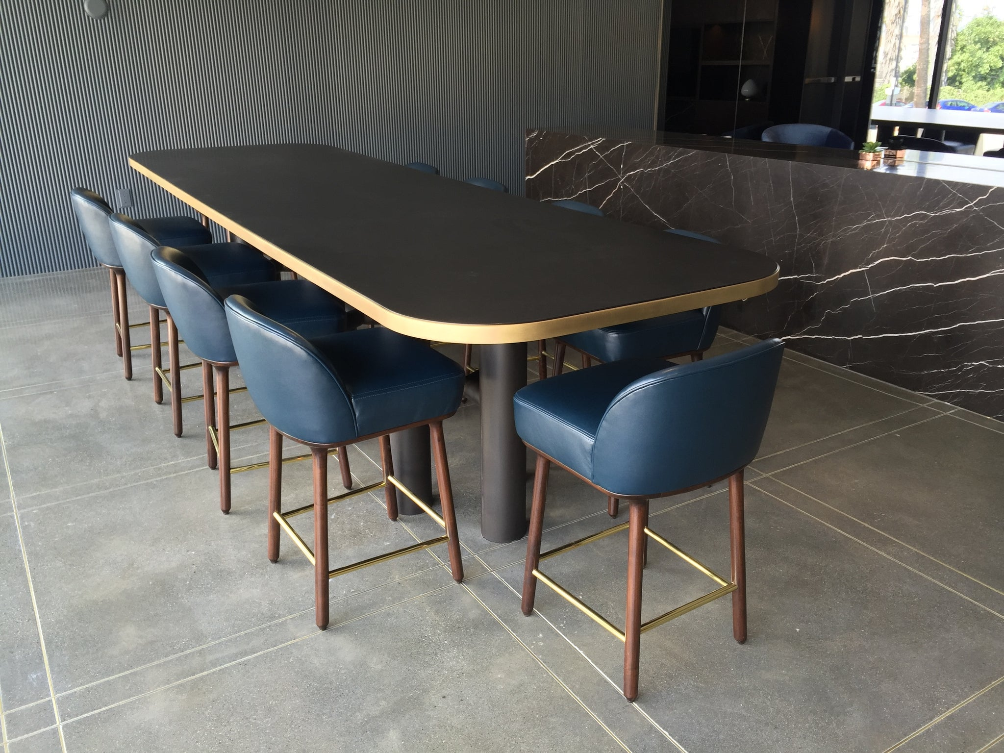 modern conference table with walnut top and brass trim with industrial metal base