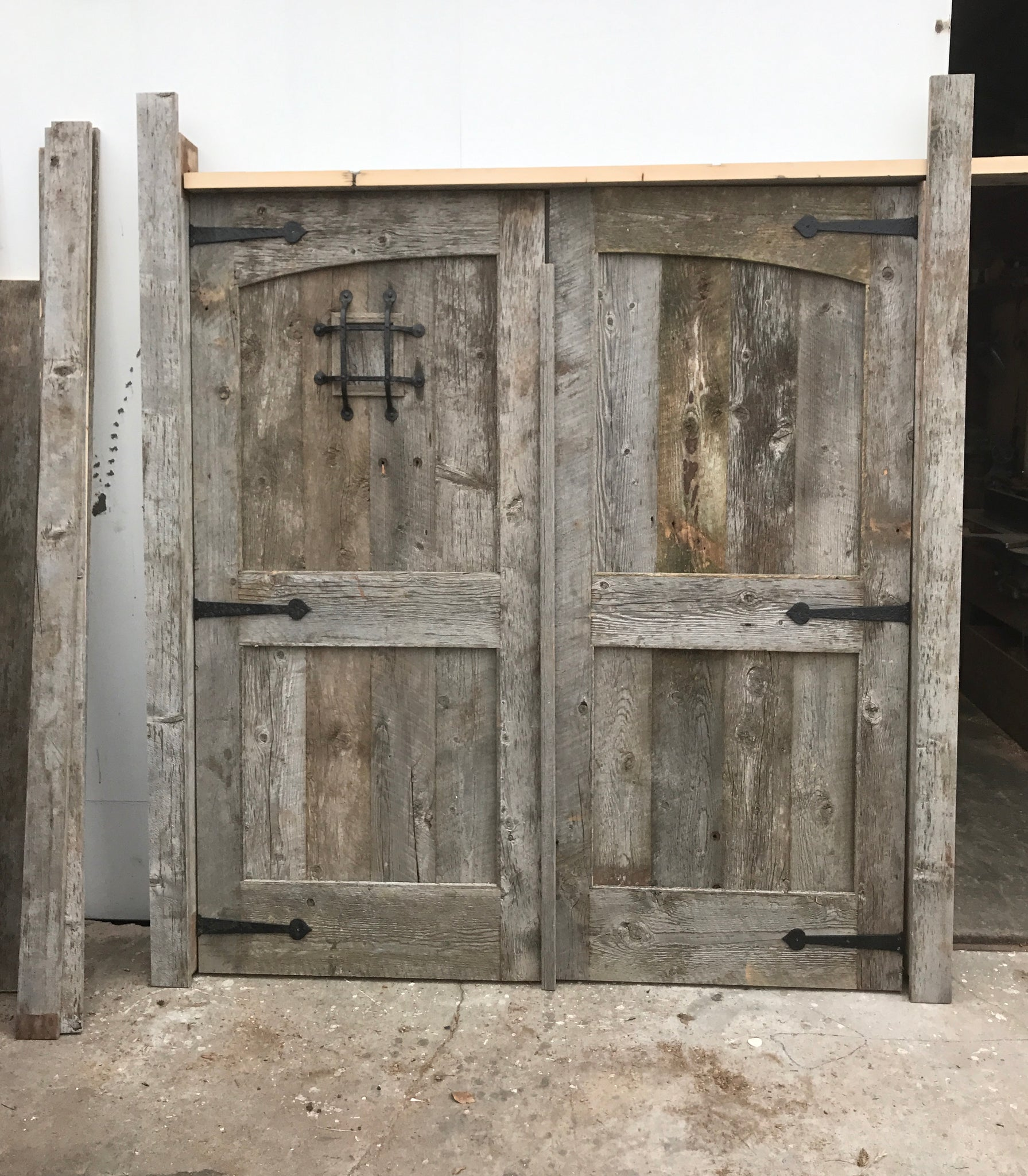 custom salvaged barn wood front doors with speak easy hardware