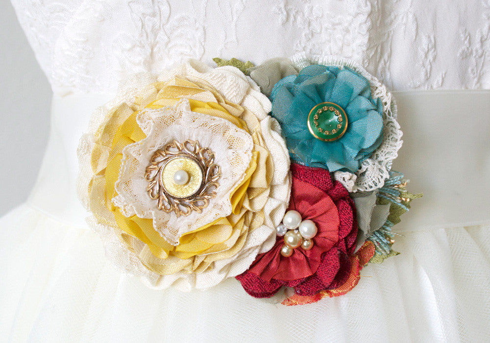 Colorful floral sash pin in yellow, teal and red
