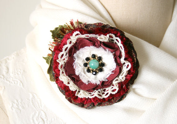 red and white fabric flower lapel pin