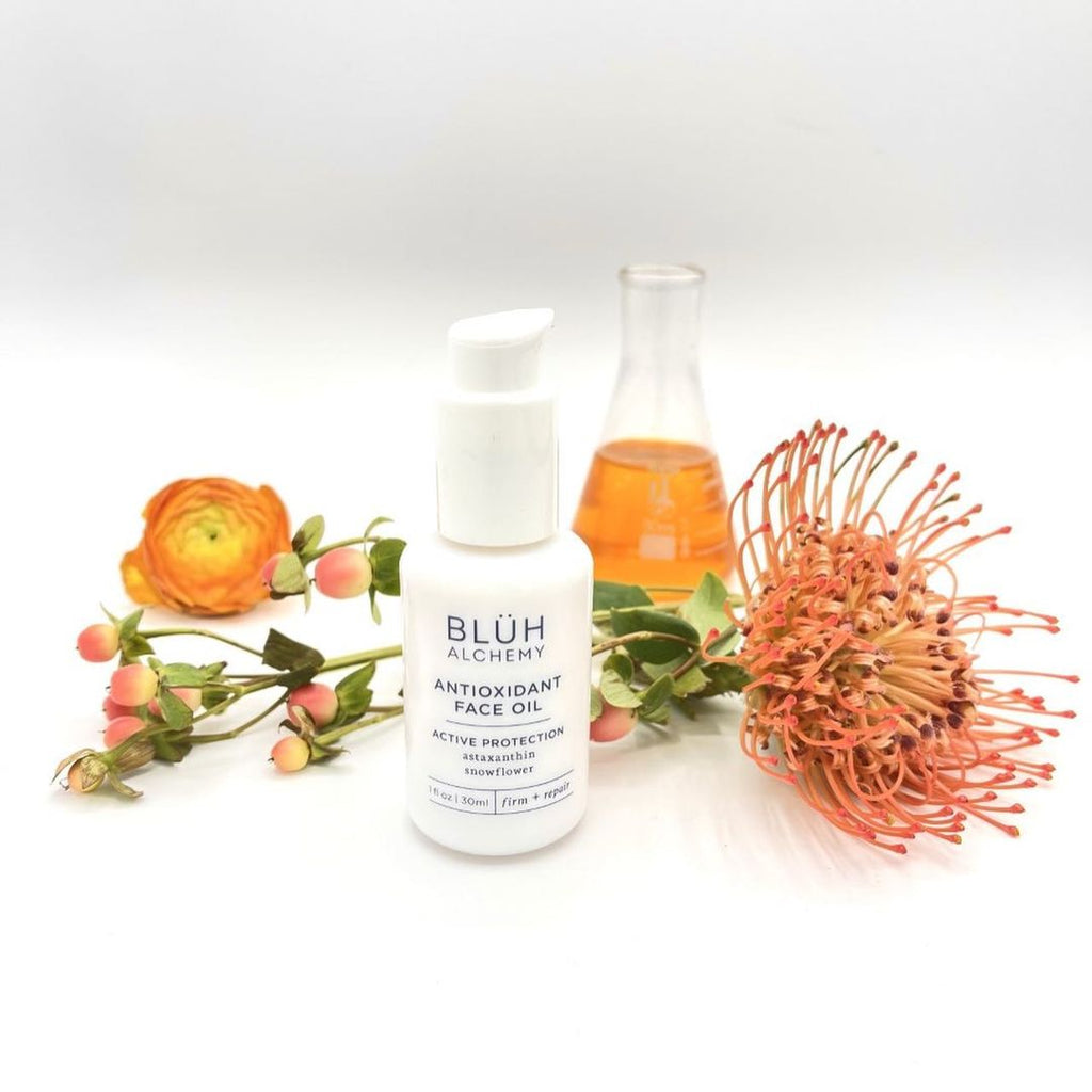On the photo is a skincare product from a brand Bluh Alchemy. It is their Antioxidant Face Oil. White packaging, white glass bottle with a pump. Writings on the bottle are in blue. There are also three different flowers in this photo and a vail with this oil which has a rich deep orange color.