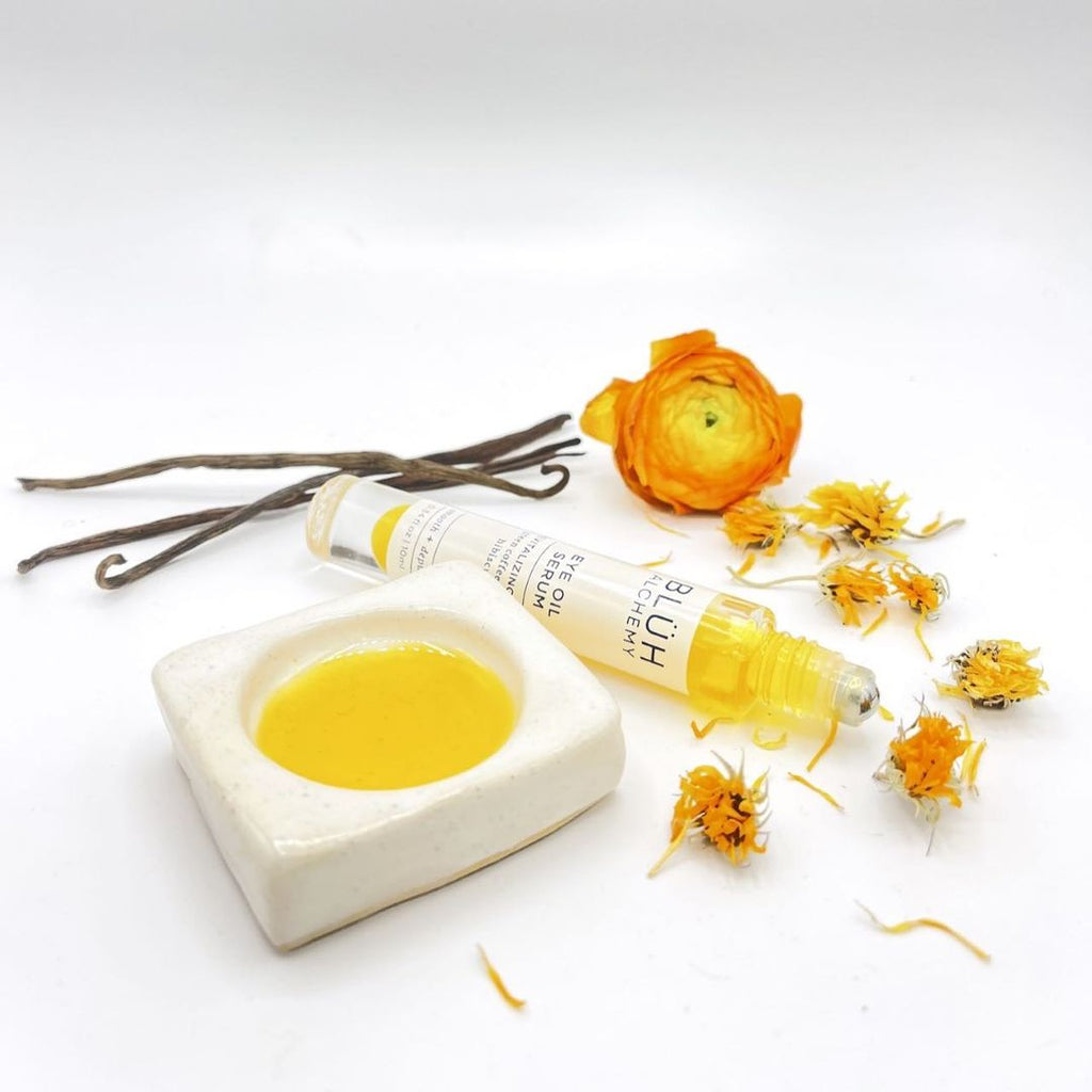 A small bottle with a roller ball applicator lays flat on a white surface. This is Eye Oil Serum by Bluh Alchemy. The clear glass bottle has a metal roller ball. The oil has a vibrant yellow colour. Around the oil are a few flowers and petals, these are calendula flowers. On the photo are also a few pieces of vanilla pods. Next to the oil is also a white ceramic dish with the oil.