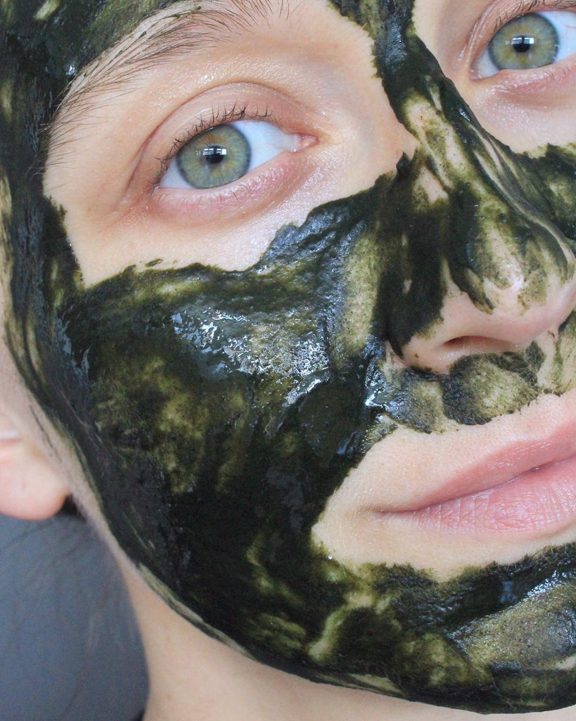 Masking selfie. A girl with green eyes is wearing a vibrant, rich, deep green face mask. The mask is mixed with water and honey. The mask is based on neem powder. This is Catharsis Face Mask by Earthwise Beauty.