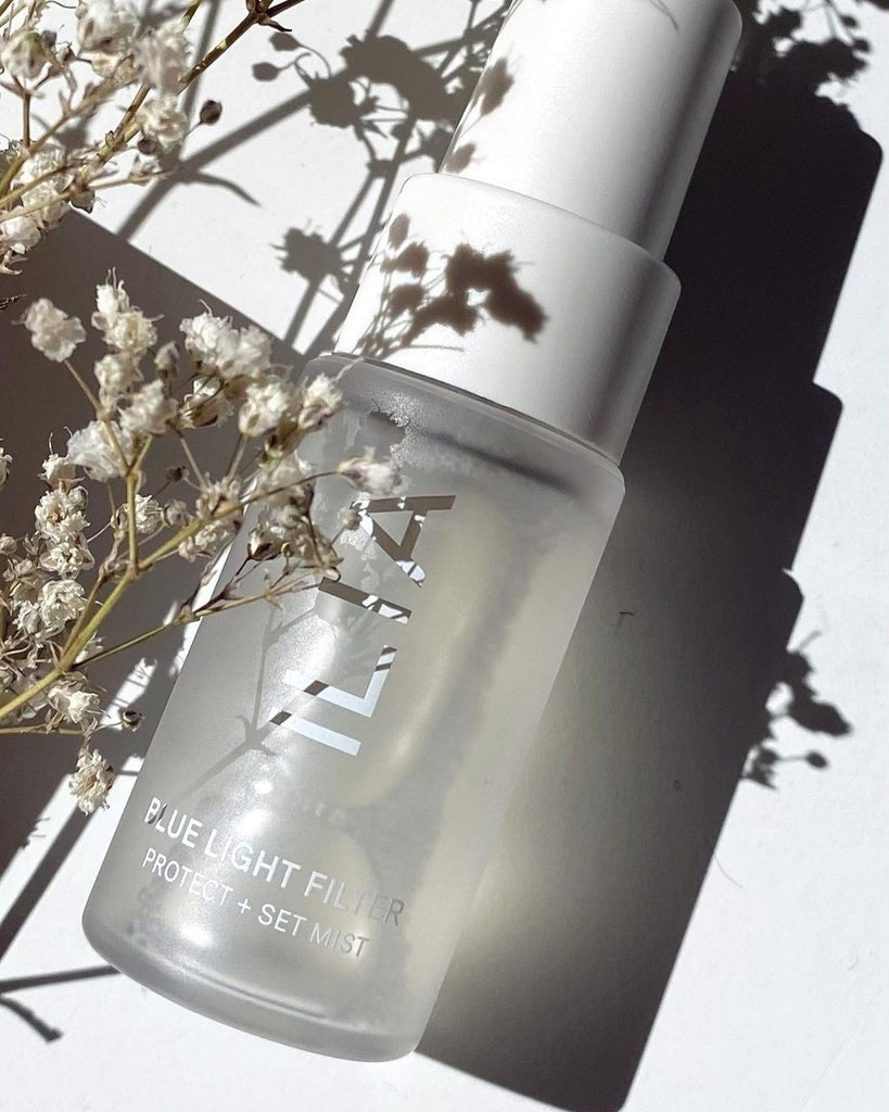 A close up of a face mist in frosted clear glass packaging with white spray mister. It lays on a white background and over it is a plant with tiny, delicate flowers in neutral color. The product is a new products from ILIA, the Blue Light Face Mist.