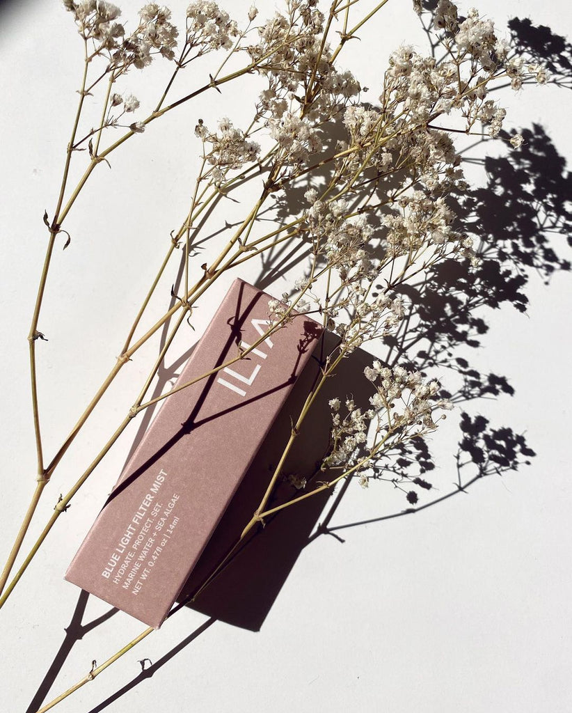 A paper box packaging in mauve rose color. It lays on a white background and over it is a plant with tiny, delicate flowers in neutral color. The product is a new products from ILIA, the Blue Light Face Mist.