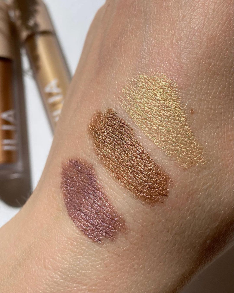 Hand swatches of eyeshadows. From top to bottom are: Gleam, an antique gold color, then Sheen, a copper bronze and Dim, Gray, a lavender with pink and purple pearl. These are Eye Tints, liquid eyeshadow that turn from cream to powder, by ILIA Beauty.