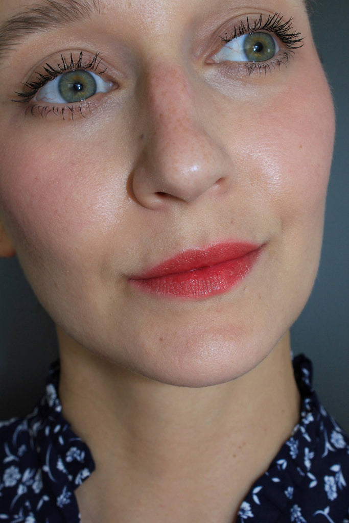 woman wearing natural looking makeup with red lipstick and red blush.