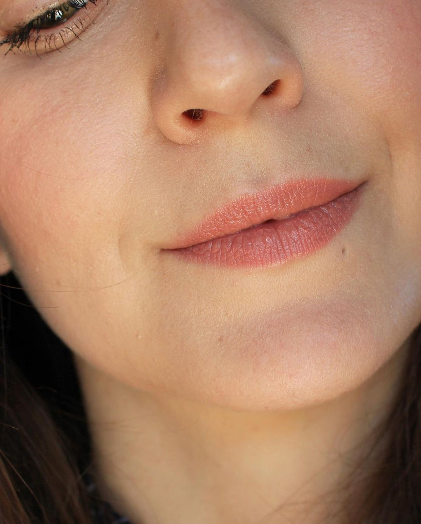 A close up of a girl and her face. It's all about the lips and her lipstick. Wearing a creamy nude color, this is the shade Barcelona. This is Velvet Lip Creme, a matte lipstick by a Canadian brand Saint Cosmetics.