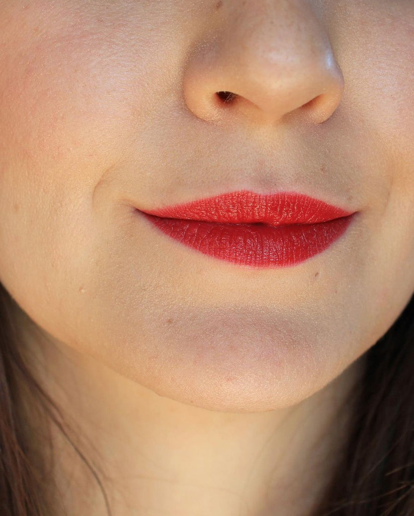 A close up of a girl and her face. It's all about the lips and her lipstick. Wearing a classic red color, this is the shade New York. This is Velvet Lip Creme, a matte lipstick by a Canadian brand Saint Cosmetics.