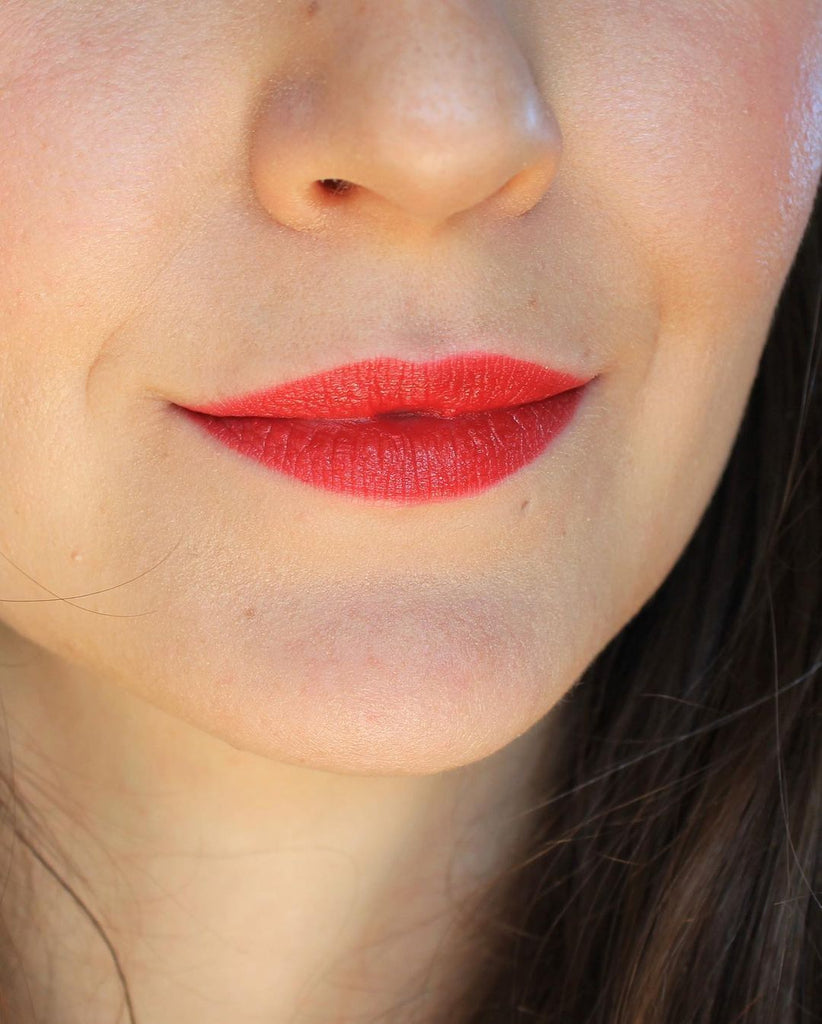 A close up of a girl and her face. It's all about the lips and her lipstick. Wearing an orange red color, this is the shade Singapore. This is Velvet Lip Creme, a matte lipstick by a Canadian brand Saint Cosmetics.