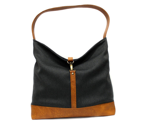 black fabric hobo shoulder bag with a brass clasp and brown vegan leather bottom