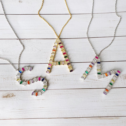 Rainbow letter necklaces on wood