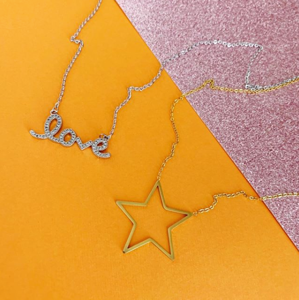 This is an image of our silver love necklace and gold stars hollow necklace on orange and pink glitter background