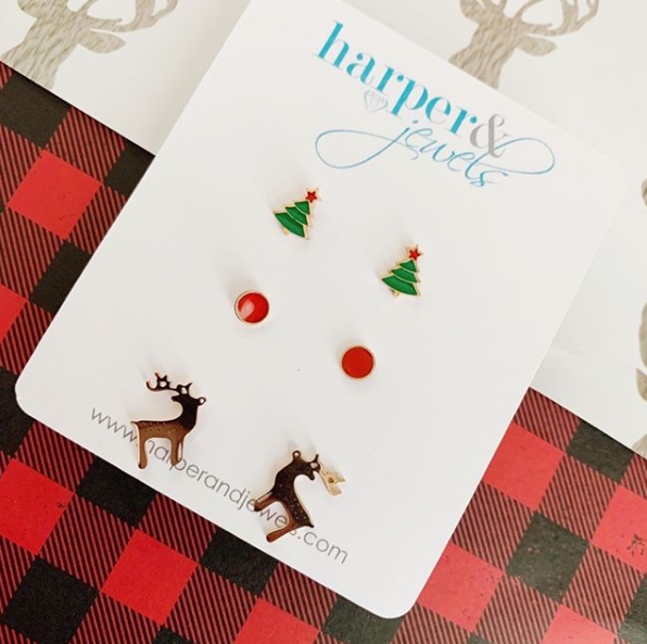 This is an image of our 3-piece christmass earring set on red buffalo plaid & reindeer paper