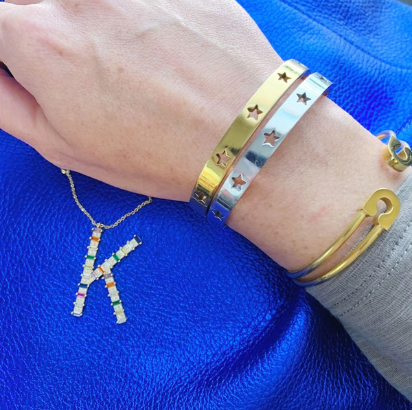 This is an image of our gold and silver star struck bangles on a blue background with a rainbow initial necklace