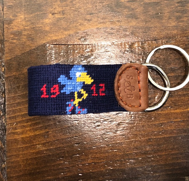 a needlepoint key fob in navy blue with the 1912 Jayhawk mascot done in red, blue, and yellow surrounded by the date. Leather end and two silver rings attached.