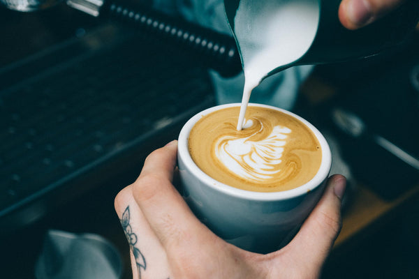 Pouring a swan info a flat white coffee