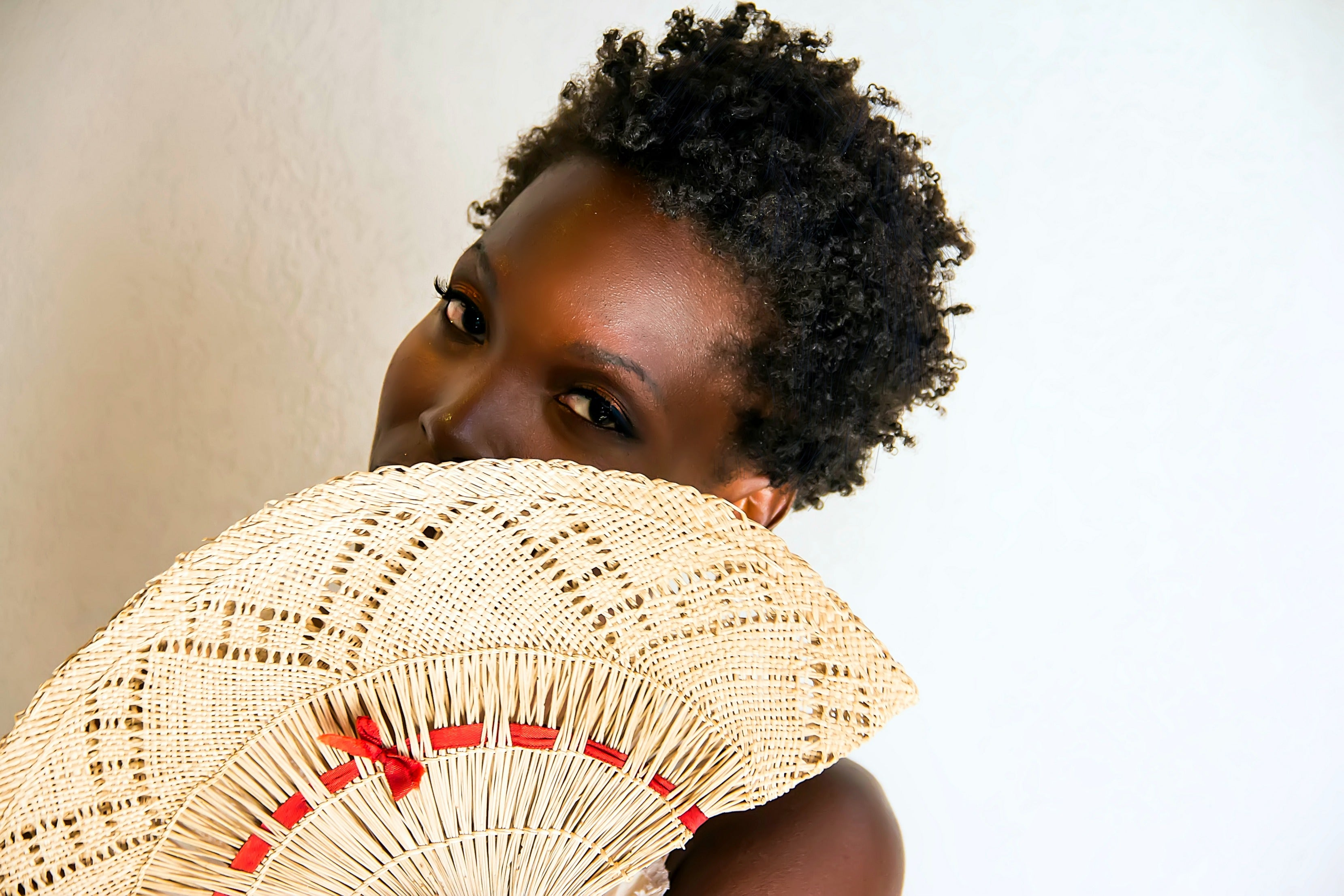 black woman, fan in front of face