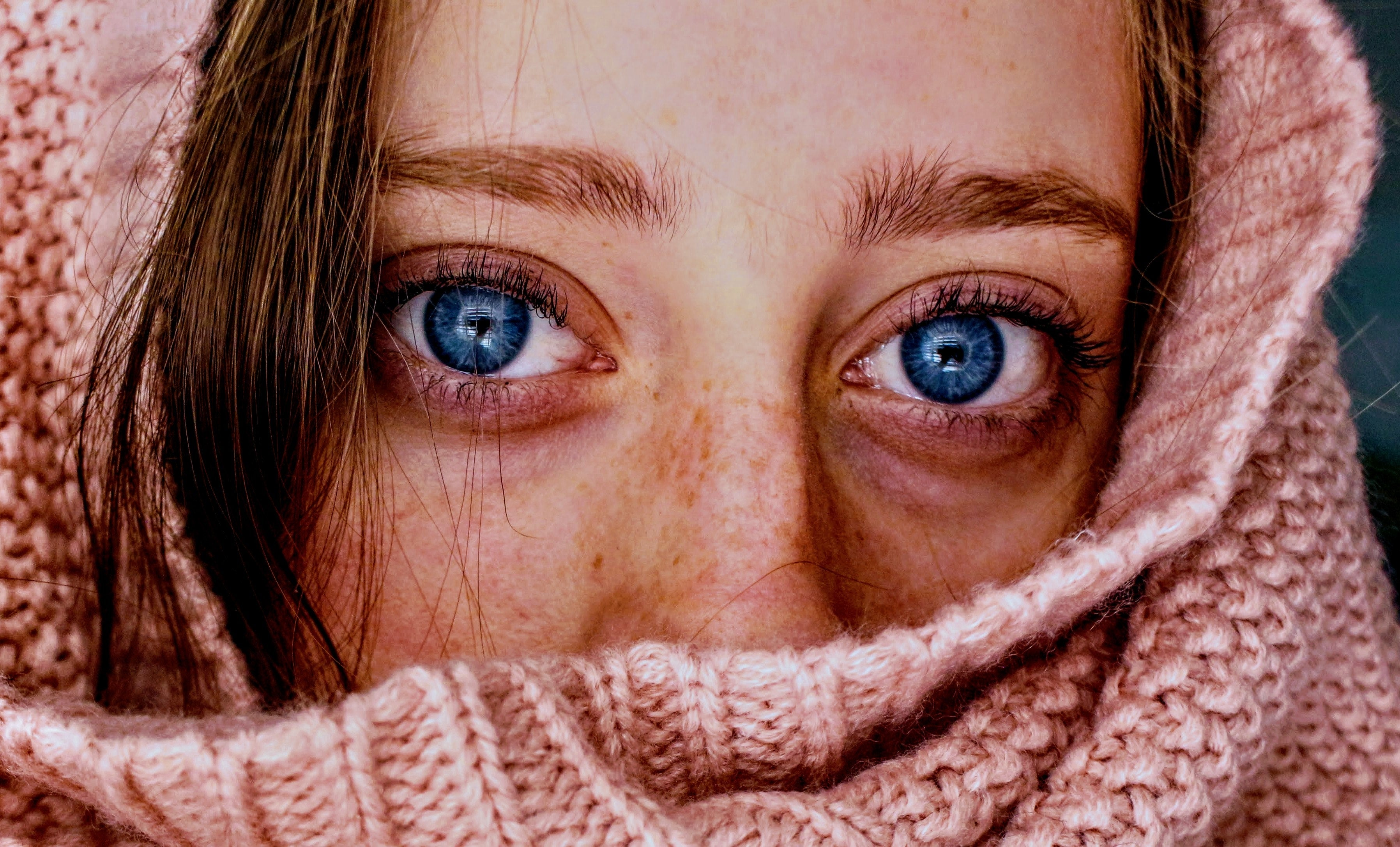 woman peaking through knit scarf