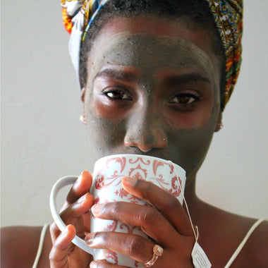 Black woman wearing JACQ's green smoothie face mask, drinking tea