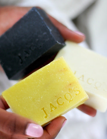 Black woman holding 2 JACQ's beauty bars, charcoal, and beige