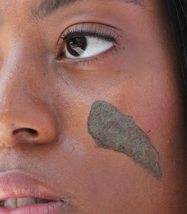 Black woman using JACQ's detoxifying charcoal face mask