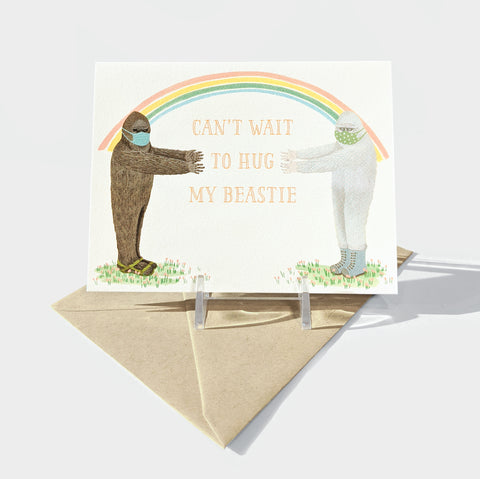 "The Library Store Folded greeting card with a kraft envelope. Image on the card depicts a Sasquatch and Yeti with face masks and a rainbow overarching them. They are reaching out toward each other and the text reads, ""Can't wait to hug my beastie""."