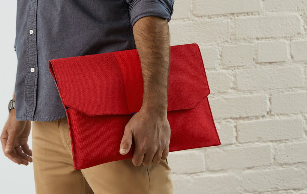 Man holding The Portfolio in Ruby Red under his arm.