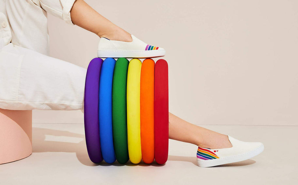 A white and multicolored striped sneaker, shown next to a rainbow prop.