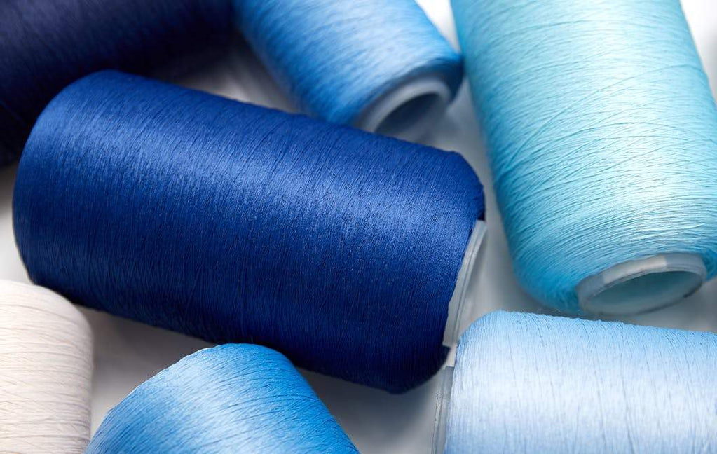Spools of Rothy's thread in different shades of blue, shown from the top.