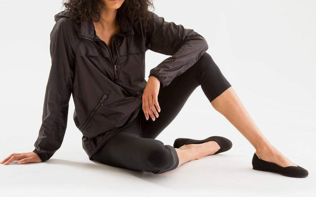Model sitting on the floor, wearing The Flat in Black.
