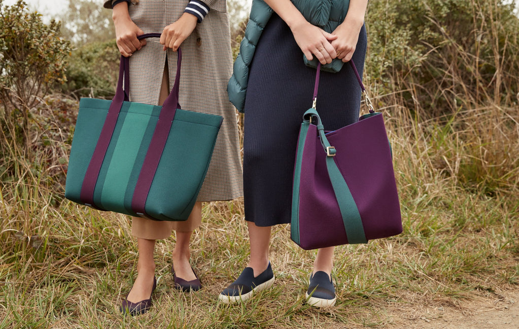 Two models standing in a field, holding The Essential Tote in Deep Spruce and The Bucket Bag in Dark Plum.