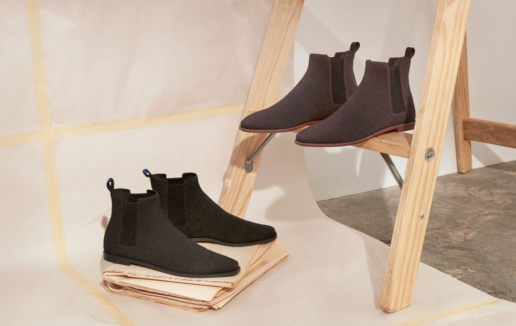 The Merino Ankle Boot in Onyx Black and Cocoa Brown, shown atop a stack of papers, and balancing on an easel frame.