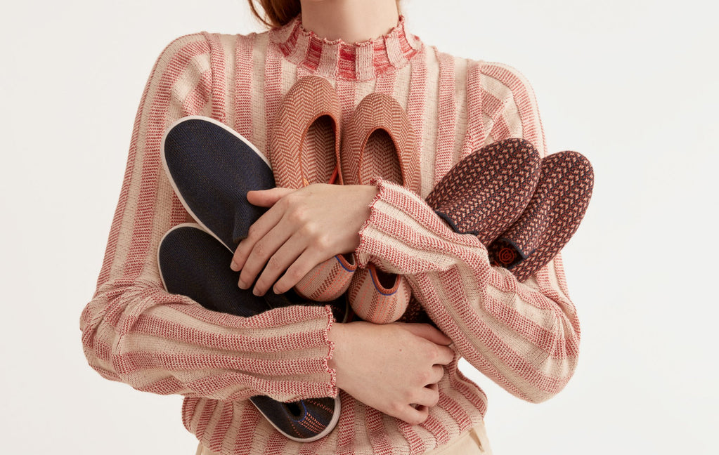 Model holding an assortment of merino shoes in her arms.