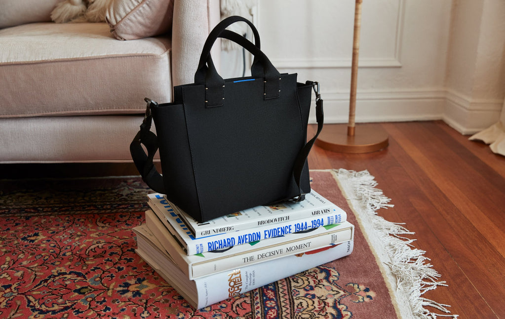 The Handbag in Total Black, shown on a stack of books atop a maroon rug.