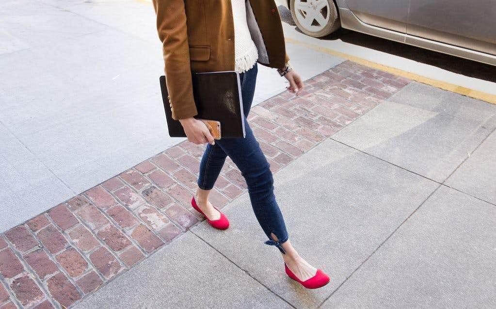 Woman walking on the sidewalk in a pair of red Rothy's flats, holding a laptop in her hands.