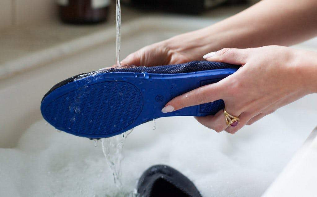 Image of woman washing her navy Rothy's flats in the sink.