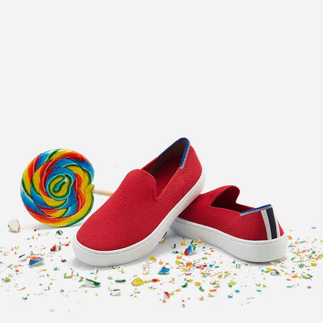 A pair of The Kids Sneaker shoe in Lollipop balancing with props.