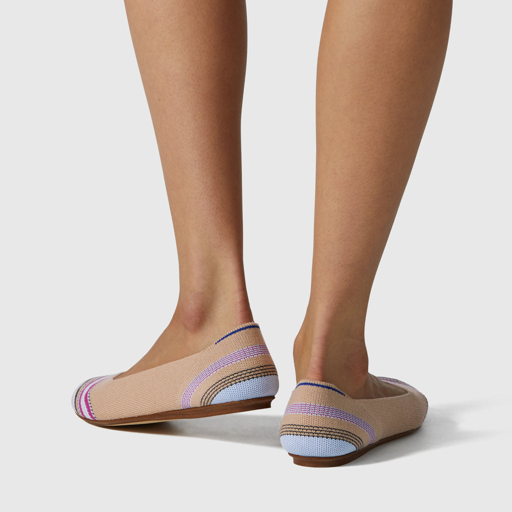 The Merino Flat round toe shoe in Camel Ribbon Stripe shown on-model at an angle.