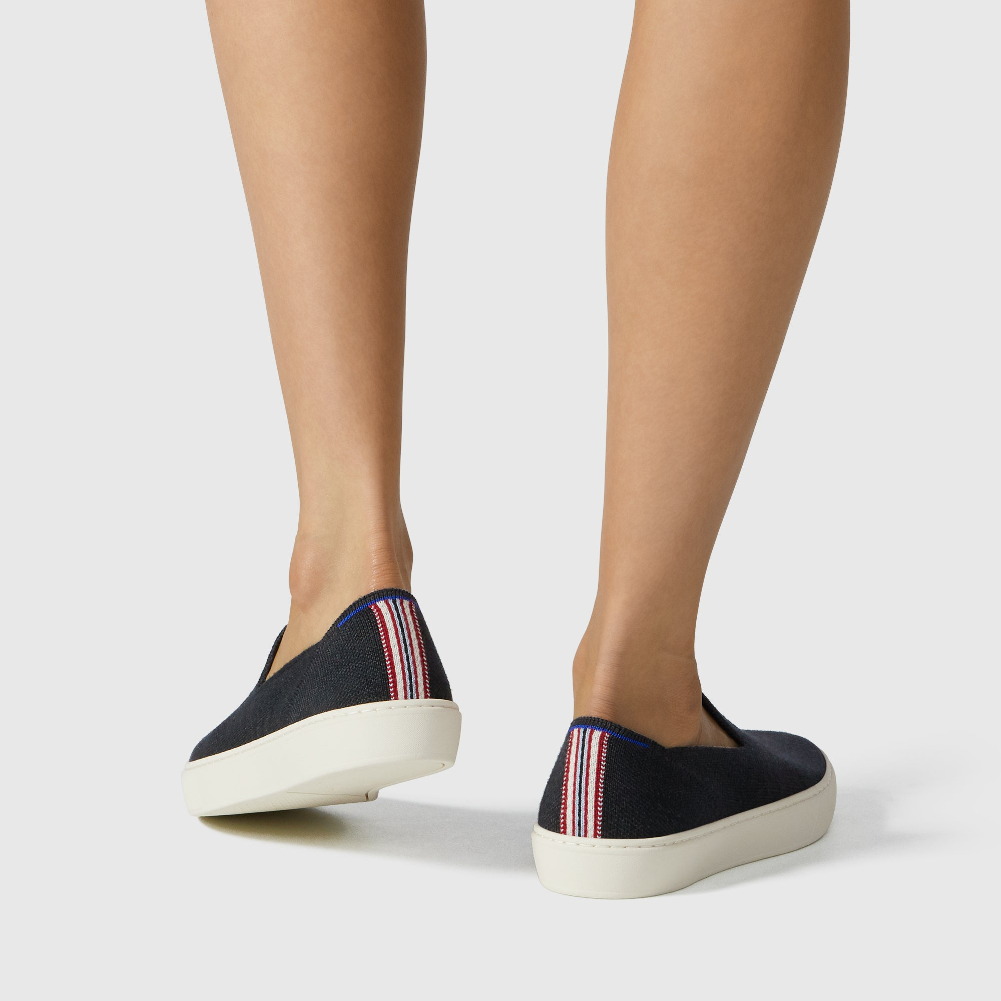 The Merino Sneaker in Soft Black shown on-model at an angle.