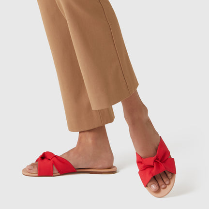 The Knot sandal in Candy Apple shown on-model at an angle.