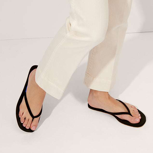 The Flip Flop sandal in Black shown on-model at an angle.