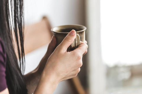 a close up of a woman holding a coffee cup