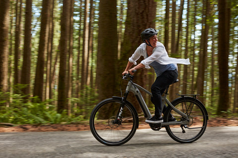Woman laughing on her e-bike in the forest