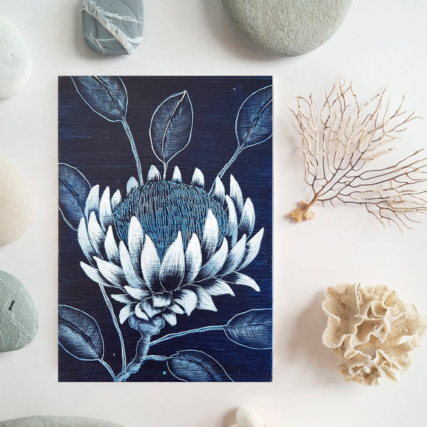 An original painting of Protea wildfower in Indigo blue and white on a wooden block laying among coral seafans and ocean smoothed stones Original one of a kind art created by Rebecca Coulter