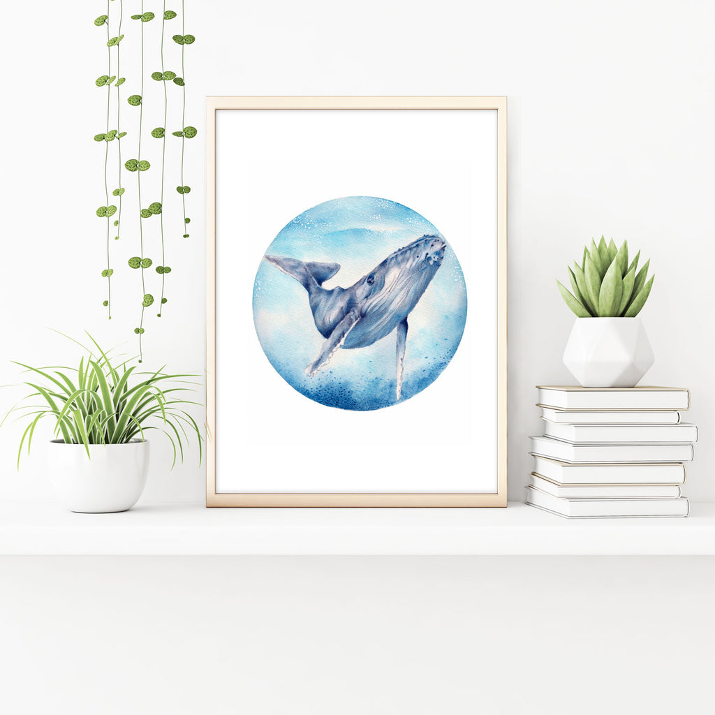 Humpback Whale art print in oak frame with indoor plants and books. Watercolour art print from Artista Style