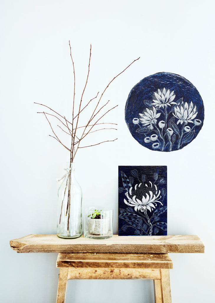 A woodblock navy blue artwork featuring a floral design inspired bu Proteas and Waratahs resting on a contemporary wooden stool with Paper wildflowers with gumnuts painted in blue and white on a handmade paper porthole displayed on the wall behind it. Original one of a kind art created by Rebecca Coulter