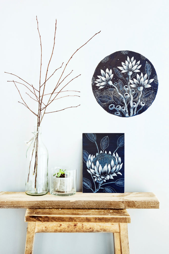 An original woodblock Indigo blue and white painting of an Australian Protea wildfower resting on a contemporary wooden stool with a blue and white floral design porthole displayed on the wall behind it. Original one of a kind art created by Rebecca Coulter